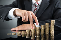 Businessman's Fingers Walking On Coins Stock Photos