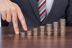 Businessman's fingers walking up stack of coins Stock Photos