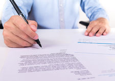 Businessman's had signing a document on desk Stock Image