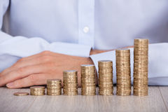 Businessman's Hand Behind Euro Coins At Desk Royalty Free Stock Images