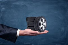 A businessman`s hand on blue chalkboard background holding four tiny car wheels. stock images