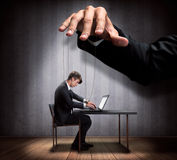 Businessman's hand controlling a worker marionette. In dark room stock photo