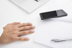 Businessman's hand on desk by cell phone, pen and book Royalty Free Stock Photos