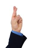 Businessman's hand with finger crossed Stock Images