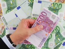 Businessman's Hand Holding 500 Euro. 500 Euro in businessman hand on background with money Stock Image