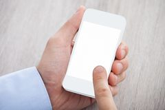 Businessman's hand holding cellphone with blank screen Royalty Free Stock Image