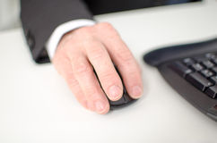 Businessman's hand holding a computer mouse Stock Photography