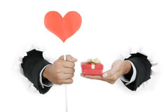 Businessman's hand holding gift and heart cutout Stock Image