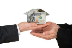 Businessman's hand holding house made of american dollar Royalty Free Stock Images
