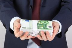 Businessman`s hand holding money, euro banknotes. Financials, investment success and profitable business concept Stock Images