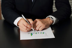 Businessman's Hand holding a pen pointing to the bar graph of Business Royalty Free Stock Photos