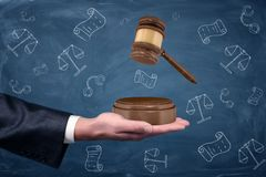 A businessman`s hand holding a sound block palm up and a wooden gavel hovering above it. Legal rights. Corporate law. Business legal protection Stock Image