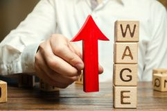 Businessman`s hand holds red arrow up near wooden blocks with word Wage. Salary increase concept. Wages rate. Revenue growth and royalty free stock photos