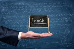 A businessman`s hand holds a small easel blackboard with a word Teach on it with equations on the background. Education and tutoring. Math problems. Science royalty free stock images
