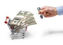Businessman's hand with a key & steel grocery cart full of money stacks - isolated on white background Royalty Free Stock Image