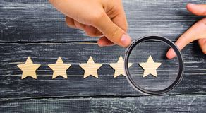 The businessman`s hand points to the fifth star. A new star, ach royalty free stock photo