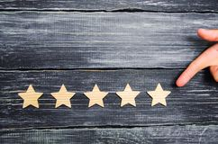 The businessman`s hand points to the fifth star. A new star, achievement.The concept of the rating of hotels and restaurants, the. Evaluation of critics and stock photo