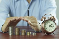 Businessman`s hand protect money coins on working wood table with alarm clock Royalty Free Stock Images