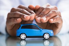 Businessman`s Hand Protecting Blue Toy Car. On The Reflective Desk stock photos