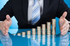 Businessman's hand protecting coins at desk Royalty Free Stock Photos