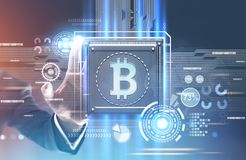 Businessman s hand reaching for bitcoin processor. Hand of a businessman in a suit reaching for a processor with a bitcoin symbol on it. Concept of modern Stock Photography