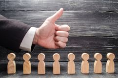 The businessman`s hand shows a thumbs-up, above the figures of workers. The concept of approval of business ideas, congratulation royalty free stock photos