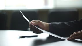Businessman's hand signing document. Man signs paper beside window. New insurance policy. Official letter to a partner.
