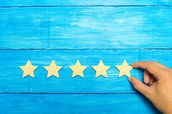 The businessman`s hand in the suit holds the fifth star. Get the fifth star. The concept of the rating of hotels and restaurants,. The evaluation of critics and stock image