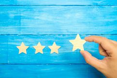 The businessman`s hand in the suit holds the fourth star. Get the star. concept of the rating of hotels and restaurants, the eval. Uation of critics and visitors stock images