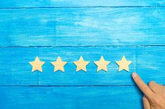 The businessman`s hand in the suit points to the fifth star. Get the fifth star. The concept of the rating of hotels and restaura. Nts, evaluation of critics and stock image
