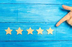 The businessman`s hand in the suit points to the fifth star. Get the fifth star. The concept of the rating of hotels and restaura. Nts, evaluation of critics and royalty free stock photos