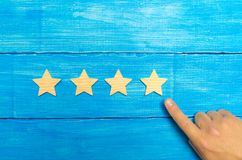 The businessman`s hand in the suit points to the fourth star. Get the fifth star. The concept of the rating of hotels and restaur. Ants, evaluation of critics royalty free stock photo