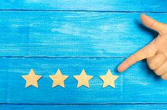 The businessman`s hand in the suit points to the fourth star. Get the fifth star. The concept of the rating of hotels and restaur. Ants, evaluation of critics stock photo