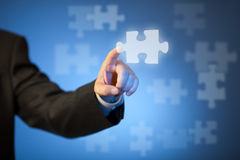 Businessman's hand touching abstract puzzle piece Stock Photography