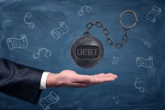 A businessman`s hand turned palm up under a large hovering iron ball with a word DEBT written on it. Credit and loan. Legal prosecution. Debt collectors Stock Images