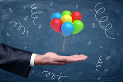 A businessman`s hand turned up with a set of colorful balloons tied together hovering above it on chalkboard background. Business celebration. Employee of the Stock Photo