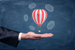 A businessman`s hand turned up and a small air balloon hovering above it on chalkboard background. Travelling business. Air travel for all. Work overseas Royalty Free Stock Photography