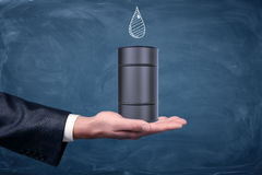A businessman`s hand turned up and a small black oil barrel standing on it with a drawn drop on chalkboard. Oil and gas business. Procurement industry royalty free stock photo
