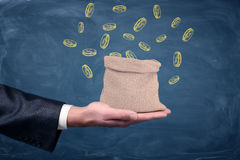 A businessman`s hand turned up and a small money bag standing on it with drawn coins on blue background. Stock Photo