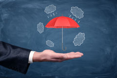 A businessman`s hand turned up and a small red umbrella hovering above it on chalkboard background. Insurance agent. Business safety. Banking options Royalty Free Stock Photography