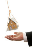 Businessman's Hand Under Dangling House stock images