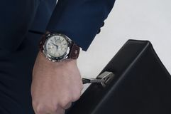 Businessman. `s hand with watch holding a briefcase Royalty Free Stock Image
