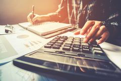 Businessman`s hands with calculator at the office and Financial Stock Photo