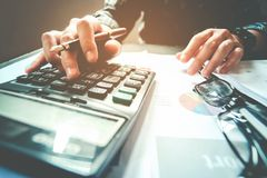 Businessman`s hands with calculator at the office and Financial Stock Images