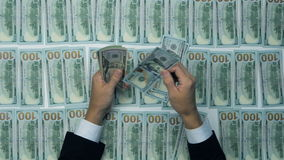 A businessman's hands counting hundred US dollar bills at a table. Dollars background. stock footage