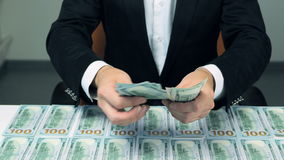 A businessman's hands counting hundred US dollar bills at a table. Dollars background. stock video