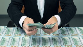 A businessman's hands counting US dollar bills and gives money into camera. stock footage