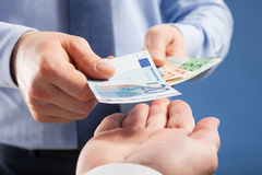 Businessman's  hands exchanging euro on blue background Stock Images