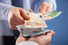Businessman's hands exchanging euro on blue background. Closeup shot stock photos