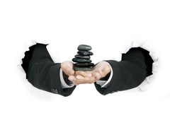 Businessman's hands holding a stack of stones Stock Images